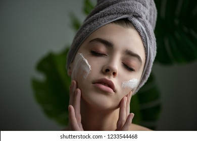 Young woman applying face cream on her face. Beauty model with perfect fresh skin and long eyelashes cares about her skin at home. Spa and Wellness, Skin Care Concept. Close up, selected focus.