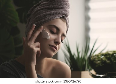 Young woman applying face cream on her face. Beauty model with perfect fresh skin cares about her skin at home. Spa and Wellness, Skin Care Concept. Close up, selected focus.  Toned.