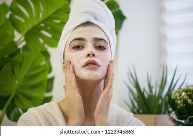 Young woman applying face mask on her face. Beauty model with  perfect fresh skin and long eyelashes cares about her skin at home or beauty salon. Spa and Wellness Concept. Close up, selected focus.