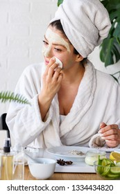 Young woman applying face mask at home. Natural skin care routine for glowing skin.