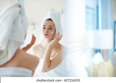 Young woman applying foundation or moisturizer on her face in front of mirror