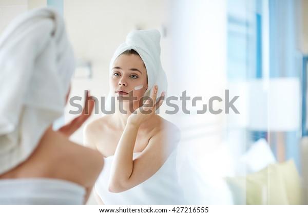 鏡の前で顔にファンデーションや保湿剤を塗る若い女性