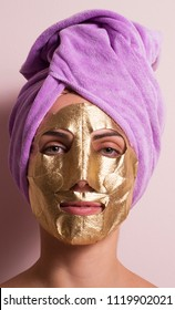 Young woman applying gold mask face treatment wearing pink towel on head.