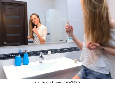Young woman applying hairspray on her wet hair in bathroom in front of the mirror.