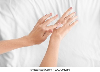 Young woman applying hand cream on light background