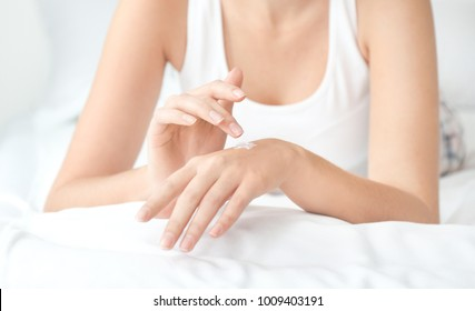 Young woman applying hand cream at home