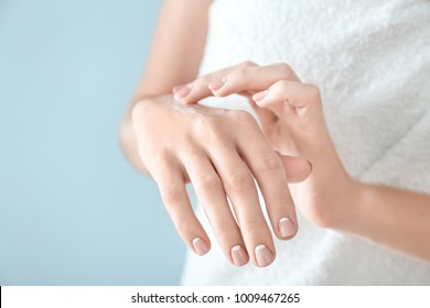 Young woman applying hand cream on color background, closeup