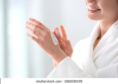 Young woman applying hand cream at home, closeup