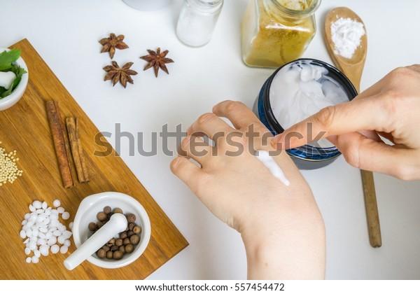 La joven está aplicando crema casera en su piel. Muchos ingredientes para cosméticos caseros en segundo plano.