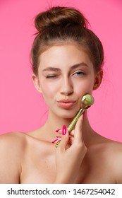 Young woman applying jade roller for massaging her face. Daily facial skincare treatment, anti age procedures for better moisturising, lymphatic drainage, skin tone improve and wrinkles reducing