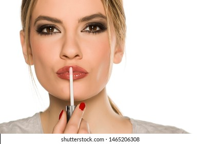 Young woman applying lip gloss on white background