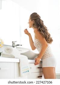 Young woman applying lip gloss in bathroom