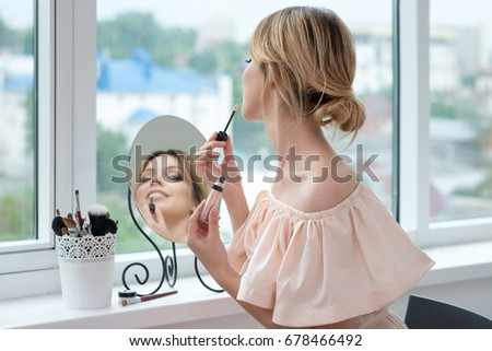Young woman is applying lip gloss makeup front of the window. Model applies professional make