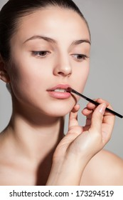 Young woman applying lipstick with an applicator