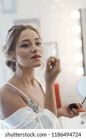 Young woman applying lipstick in bathroom.