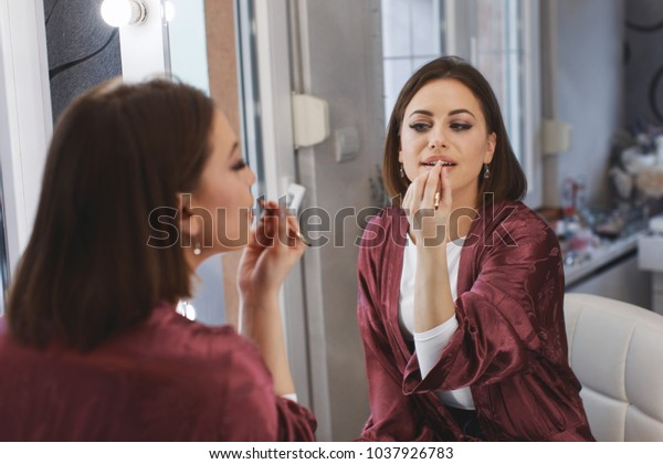 Young woman applying lipstick at home