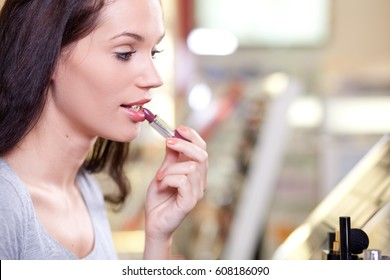 Young woman applying lipstick in make up store