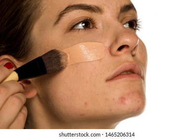 Young woman applying liquid foundation on white background