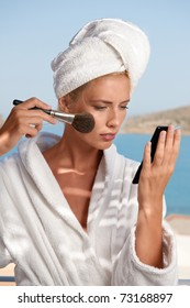 Young woman applying make up with white towel on her head