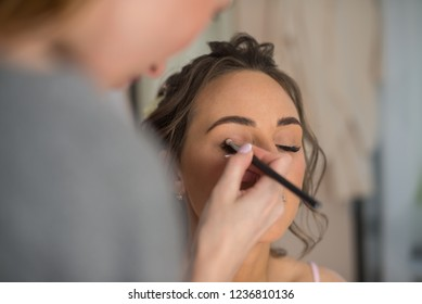 young woman applying makeup, eyebrows and eyelashes