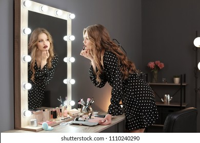 Young woman applying makeup near mirror in dressing room