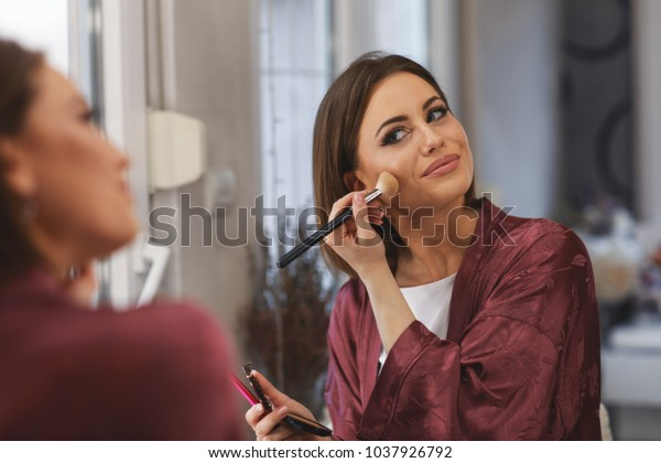Young woman applying makeup on face at home
