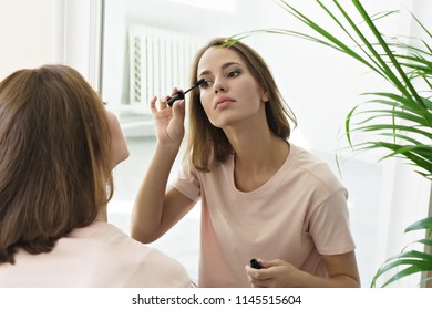 young woman applying mascara in front of mirror at home