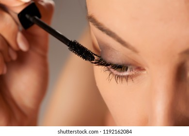 Young woman applying mascara on white background