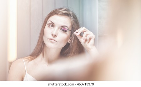Young woman applying mascara on long eyelashes in front of a bathroom mirror
