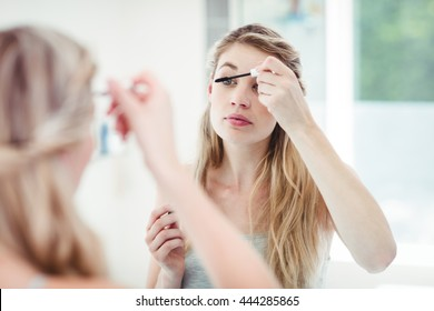 Young woman applying mascara while looking in mirror