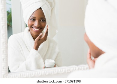 Young woman applying moisturizer to her skin in the bathroom
