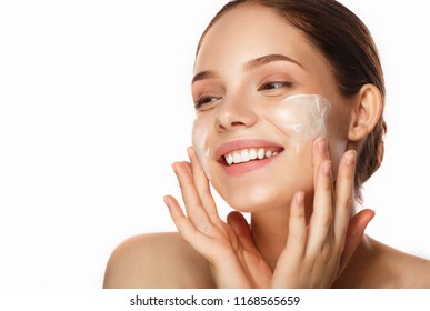 young woman applying moisturizing cream on her face.  Skin care concept