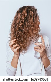 Young woman applying moisturizing spray to her curly hair on white studio background.