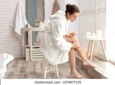 Young woman applying natural scrub onto her skin in bathroom
