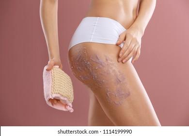 Young woman applying natural scrub on her body against color background