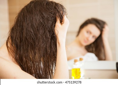 Young woman applying oil mask to hair tips in front of a mirror; haircare concept