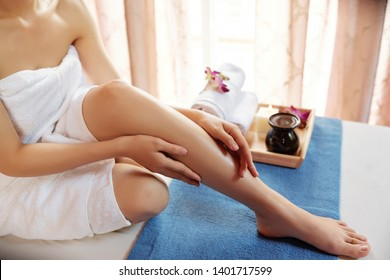 Young woman applying oil on her body and massaging herself