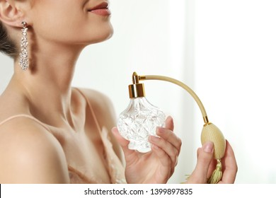 Young woman applying perfume against blurred background, closeup. Space for text