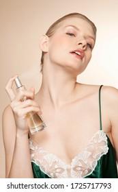 Young woman applying perfume, studio shot