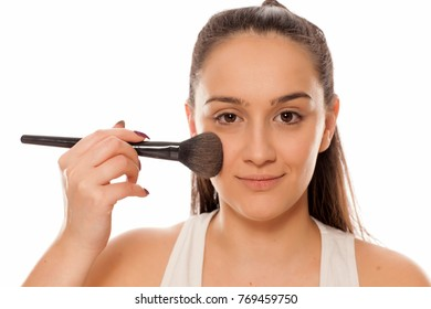 young woman applying a powder foundation on her face with a brush