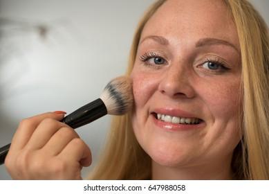 Young woman applying powder make-up