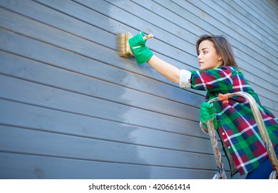 Young woman applying protective varnish or paint on wooden house tongue and groove cladding elevation wall. House improvement  diy concept.