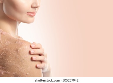 Young woman applying scrub on shoulder against color background. Skin care concept.