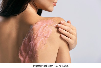 Young woman applying scrub on shoulder on grey background