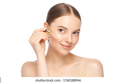 Young woman applying serum to her face, looking away, isolated on white background. Beautiful model girl with perfect clean fresh skin.Treatment or cosmetic ads concept