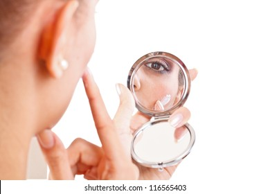 Young woman applying some cream on her face
