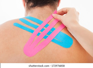 Young Woman Applying Special Physio Tape On Man's Back