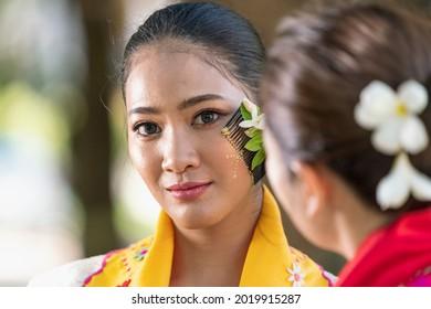 Young woman applying Tanakas powder. Burmese women are applying powder according to the Burmese culture. Southeast Asian young girls with burmese traditional dress.