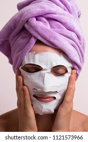 Young woman applying white mask face treatment wearing pink towel on head.