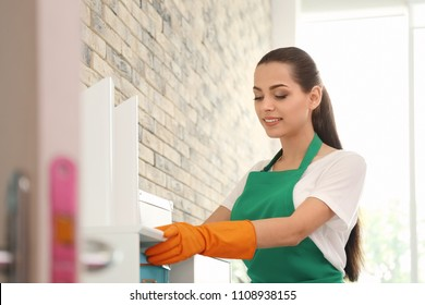 Young woman in apron and gloves cleaning office